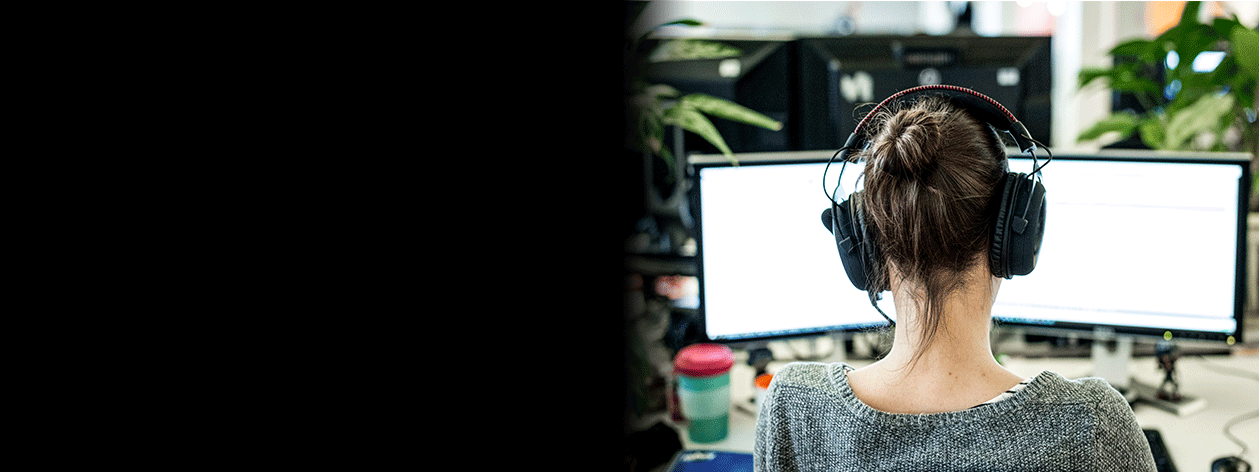 Woman facing a computer screen wearing headphones