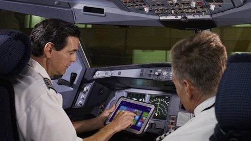 Photo of two airline pilots looking at a tablet