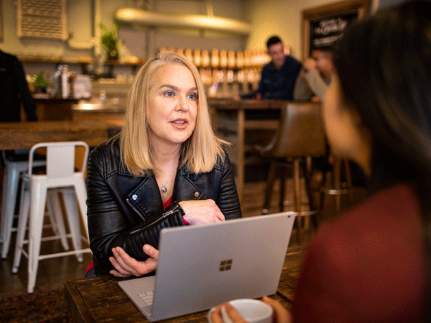 Una mujer habla frente a un portátil