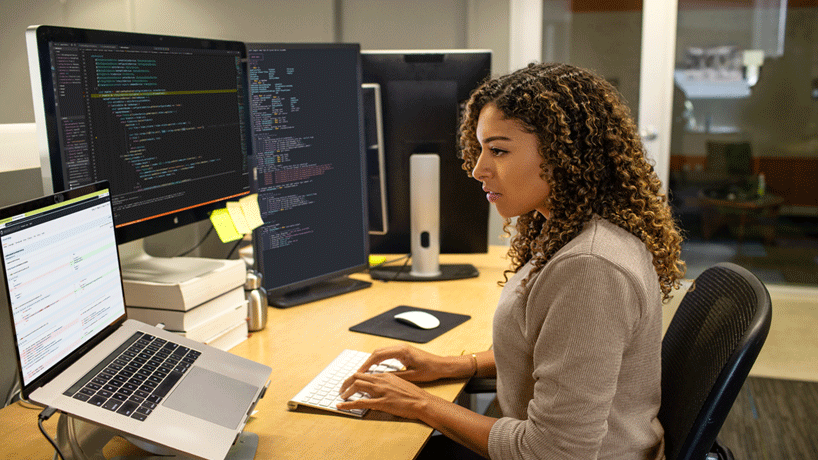 Photo of a woman working in front of monitors